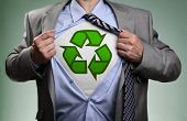 picture of environmental conservation  - Businessman in classic superman pose tearing his shirt open to reveal t shirt with recycling symbol concept for recycling and environmental conservation - JPG