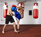 stock photo of kickboxing  - Two young kickbox fighters training in the gym - JPG