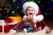 picture of santa baby  - funny baby dressed in Santa Claus hat on bright festive background - JPG
