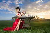stock photo of tea party  - Young woman posing as magnificent card queen from wonderland at mystic tea - JPG