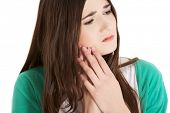pic of bruises  - Teen woman pressing her bruised cheek with a painful expression as if she - JPG