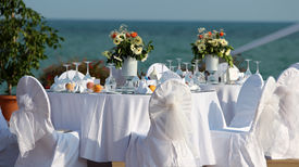 stock photo of wedding  - Wedding Chairs and covers at an outdoor wedding. Elegant Outdoor Wedding Table with Sea Views. Table set for an event party or wedding reception. - JPG