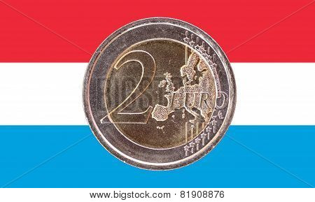 Common Face Of Two Euro Coin On Flag Of Luxembourg