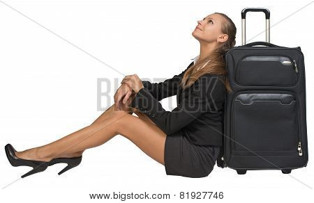Businesswoman sitting next to front view suitcase with extended handle, looking upwards