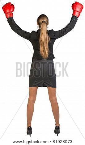 Businesswoman wearing boxing gloves wins. Rear view