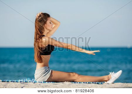 Young woman performs stretching exercises sitting on the beach
