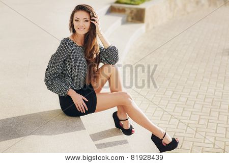 Portrait of a beautiful young woman, sitting on the stairs in the city.