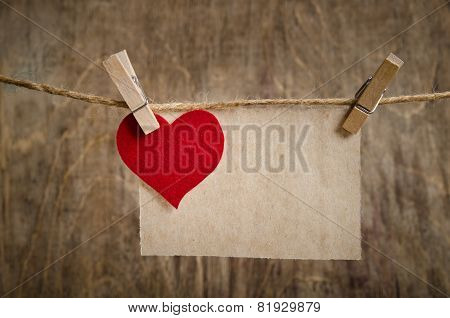 Red Fabric Heart With Sheet Of Paper Hanging On The Clothesline. On Old Wood Background.