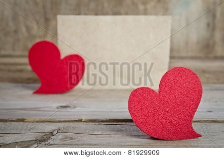 Two Red Fabric Hearts Standing On A Wooden Board. On Old Wood Background.
