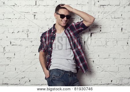 Young handsome attractive man hipster with sunglasses his hand in the hair smiles
