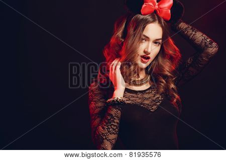 Portrait of a beautiful model with a red bow on a dark background.