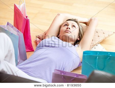 Cute woman lying on the floor between shopping bags