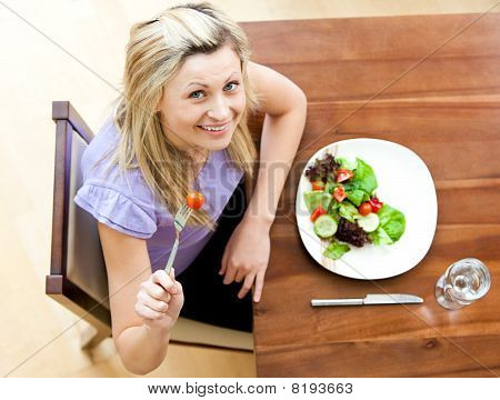 Radiant woman holding a tomatoe sitting at a table