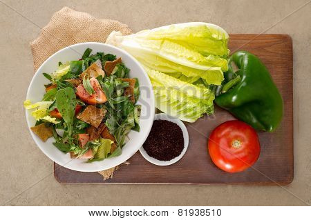 Plate of traditional Arabic salad fattouch on a wooden plate