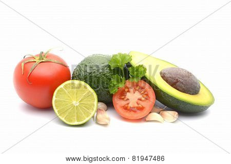 Fresh Avocado Surrounded By  Tomato, Garlic And Lime On White Background