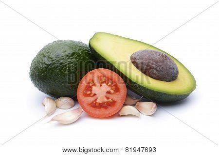 Fresh Avocado Surrounded By  Tomato And Garlic On White Background
