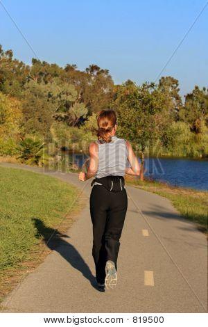 Woman jogging along a river at sunset