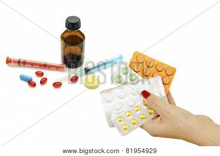 Pills In Hand As Well As A Variety Of Pharmacological Drugs And Syringes