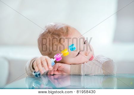 Little boy in the living room holding watercolors