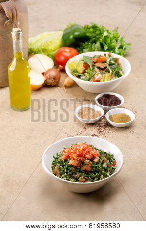 Plates of traditional Arabic salad fattouch and tabbouleh on a rustic background