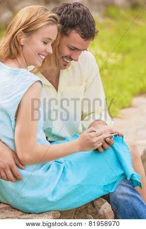 Two Young Caucasian Happy And Smiling Lovers Together Embraced. Using Pda Pocket Assistant