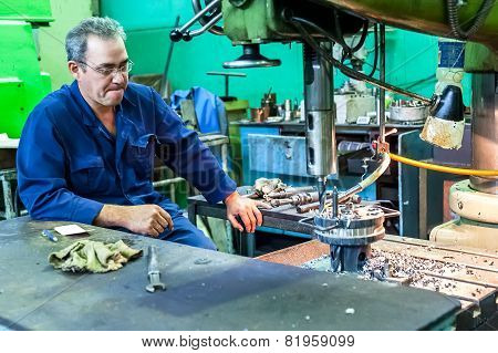 Senior milling machine operator works at machine