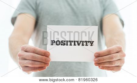 Man In A Grey Shirt Holding Up A White Card Saying Positivity