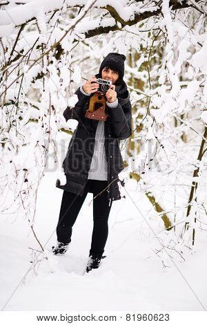 Girl with a vintage camera in the winter forest