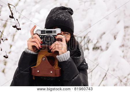 smiling girl photographed on a camera in winter forest