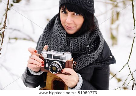 Beautiful brunette girl with a vintage camera