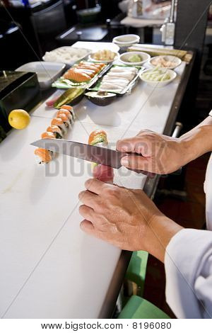 Chef In Japanese Restaurant Preparing Sushi Rolls
