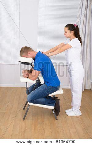 Masseuse Massaging Man's Shoulder