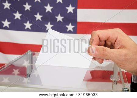 Person Casting A Ballot In Front Of Usa Flag