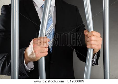 Businessman Bending Bars Of Jail
