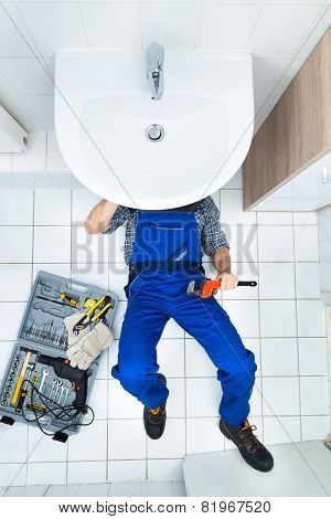 Plumber Repairing Sink In Bathroom
