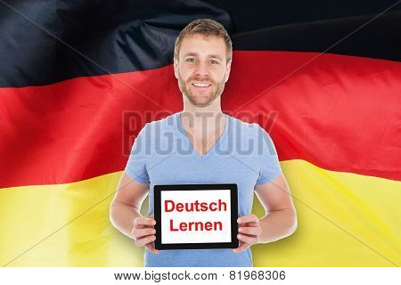 Man Holding Digital Tablet With Learn German Text