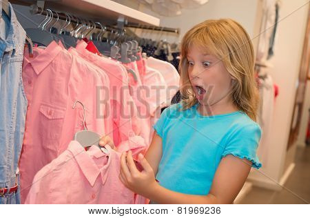 Little girl shopping in clothes store. Shocked mouth opened child looking at price tag. Girl chooses
