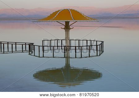 The gazebo for protection from the sun reflected in Dead Sea water at sunset