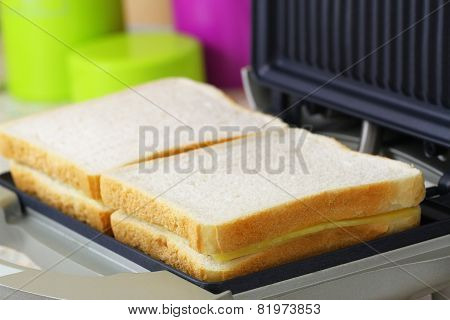 Toast with cheese and ham in toaster, closeup