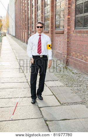 Blind Man Walking On Sidewalk Holding Stick