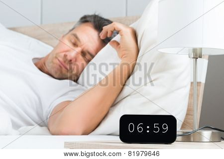 Man On Bed With Clock On Nightstand