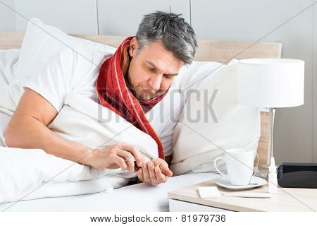 Sick Man Having Medicine In Bed