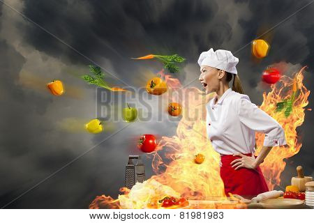 A disgruntled chef is shouting at somebody, around blazing ingredients
