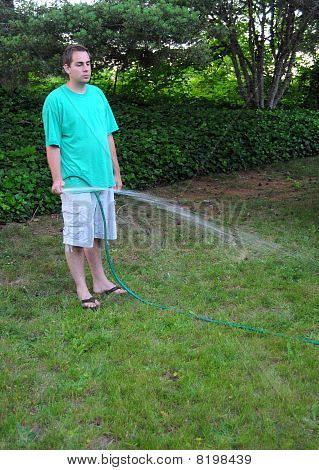 Man Watering His Grass Lawn With A Hose