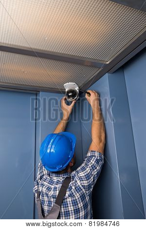 Technician Adjusting Security Camera
