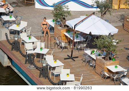 Women, Tables, Chairs And Olive Trees