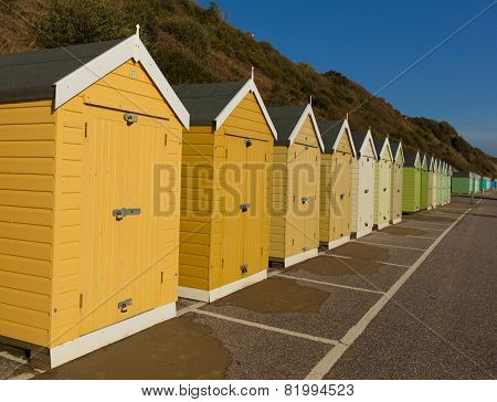 Gold yellow and brown beach huts in a row with blue sky traditional English structure