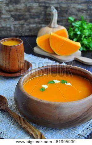 Vegetarian pumpkin soup in dark wooden bowl on a wooden table