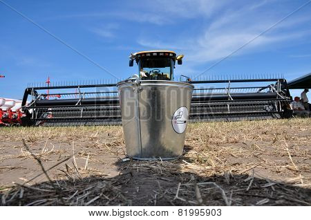 metal bucket standing on dry ground and harvesters