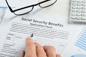 image of social-security  - Close-up Of Hand With Pen And Eyeglasses Over Social Security Benefits Application Form